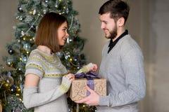 Человек делает подарок к женщине для рождества Стоковое Изображение RF