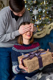 Человек делает сюрприз к женщине для рождества Стоковое Фото