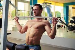 Человек делает тренировки плеча на машине кабеля Стоковое Фото