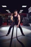 Человек делает тренировки разрабатывая с веревочкой в спортзале стоковые изображения rf