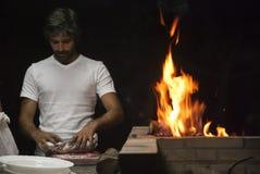 Человек делая барбекю к ноча Стоковые Фото