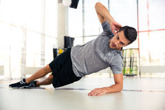 Человек делая бортовую планку на спортзале Стоковое Фото