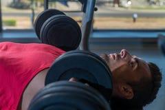 Человек делая прессы комода уклона с гантелями в спортзале Стоковая Фотография RF
