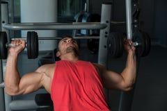 Человек делая прессы комода уклона с гантелями в спортзале Стоковое Фото