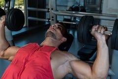 Человек делая прессы комода уклона с гантелями в спортзале Стоковые Изображения