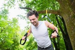 Человек делая спорт слинга тренера подвеса стоковое изображение rf