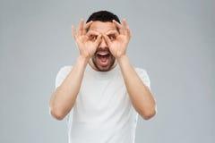 Человек делая стекла пальца над серой предпосылкой стоковое изображение
