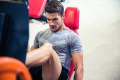 Человек делая тренировки ног на тренажере Стоковые Изображения