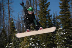 Человек делая холм скачки фокуса сноубординга вниз снежный в горах Стоковое Изображение RF