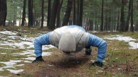 Человек делая хлопать нажимает поднимает снаружи в лесе Crossfit traing outdoors видеоматериал