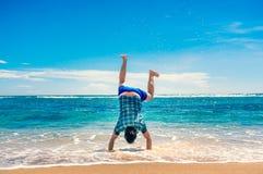 Человек делая handstand на пляже Стоковое Изображение