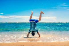 Человек делая handstand на пляже Стоковые Фото