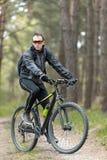Человек едет велосипед в лесе Стоковые Фото