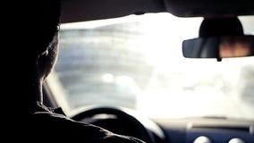 Человек едет в автомобиле через город на предпосылке солнца весны яркого, защищает ваши глаза от его Slowmotion видеоматериал