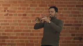 Человек джаза играя его трубу с СТОПОМ дорожного знака видеоматериал