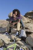 Человек женщины обнимая пока сидящ на утесах Стоковые Фотографии RF