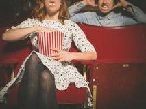 Человек женщины досадный в кино путем еда попкорна стоковые фотографии rf