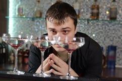 Человек заканчивать 3 стекла коктеиля стоковое изображение