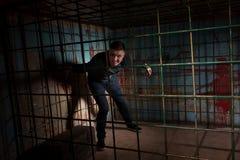 Человек заключенный в турьму в клетке металла с кровью splattered behi стены Стоковая Фотография RF