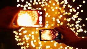 Человек записывает видео- фейерверки на умном телефоне сток-видео