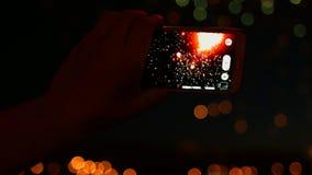 Человек записывает видео- фейерверки на умном телефоне акции видеоматериалы