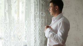 Человек застегивая белую рубашку