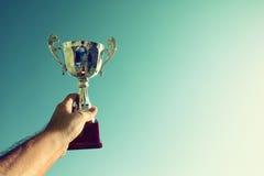Человек задерживая чашку трофея как победитель против голубого неба стоковые фото