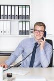 Человек знонит по телефону на столе в офисе стоковое изображение rf