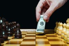 Человек играет шахмат с 100 долларами счета Стоковое Изображение RF