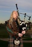Человек играет шотландские волынки на сумраке Стоковое Фото