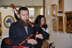 Человек играет шотландские волынки Стоковые Изображения