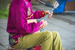 Человек играя балалайку Стоковая Фотография