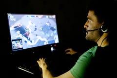 Человек играя видеоигру в темной комнате стоковая фотография