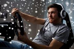 Человек играя видеоигру гонок автомобиля дома Стоковые Изображения RF