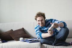 Человек играя видеоигру на софе Стоковое Изображение