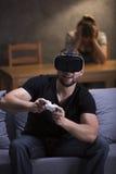 Человек играя видеоигры используя VR Стоковые Изображения