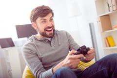 Человек играя видеоигры и держа кнюппель Стоковое Фото