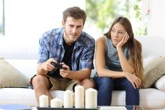 Человек играя видеоигры и подругу пробуренные рядом с стоковая фотография