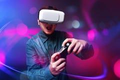 Человек играя видеоигры нося изумлённые взгляды vr стоковое фото
