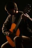 Человек играя гитариста классики гитары Стоковые Фото