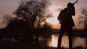Человек играя гитару на силуэте захода солнца акции видеоматериалы