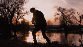 Человек играя гитару на силуэте захода солнца сток-видео