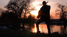 Человек играя гитару на силуэте захода солнца видеоматериал