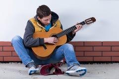 Человек играя гитару на улице Стоковое Изображение RF