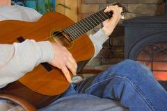 Человек играя гитару перед огнем Стоковое Изображение RF