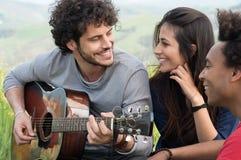 Человек играя гитару с друзьями Стоковая Фотография RF