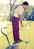 Человек играя гольф идет ударить шарик на поле для гольфа Стоковые Фотографии RF