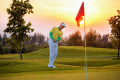 Человек играя гольф против захода солнца Стоковые Изображения