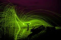 Человек играя жезл огня в предпосылке текстуры Стоковое Изображение