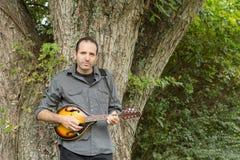 Человек играя мандолину против дерева Стоковая Фотография RF